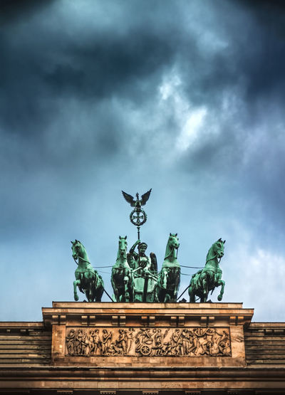 The Brandenburger Gate in Berlin, Germany Animal Animal Representation Architecture Berlin Brandenburger Tor Building Exterior City Gate Cloud - Sky Colors Day Dramatic Sky Horse No People Outdoors Sculpture Sky Statue Travel Destinations Discover Berlin