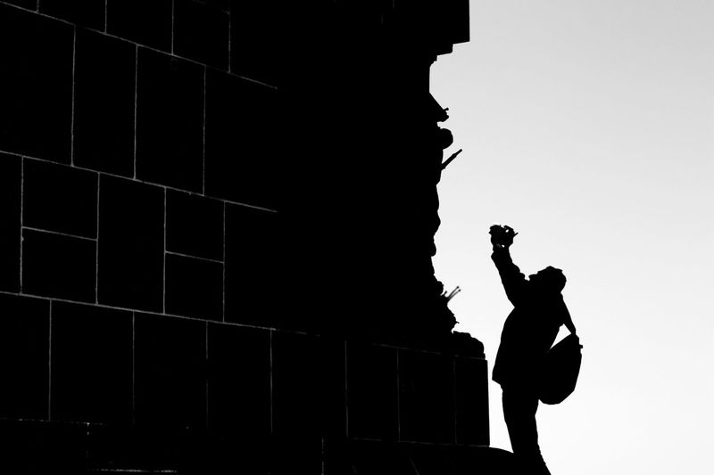 Low angle view of silhouette man standing by wall