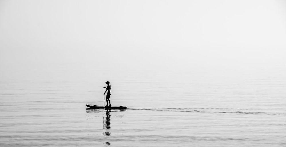 Woman paddleboarding on ocean