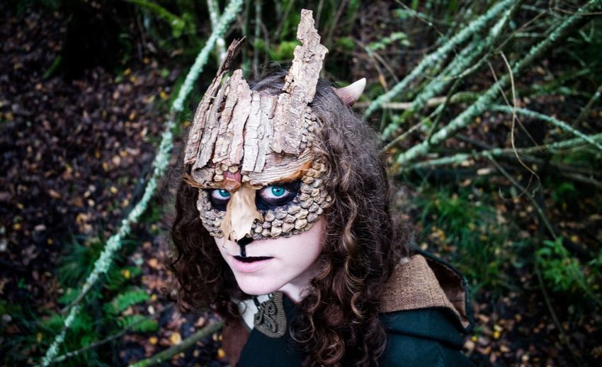 Portrait Of Young Woman Wearing Mask In Forest