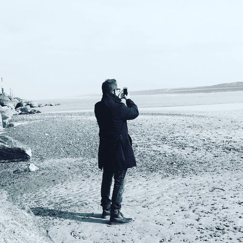 Rear view of man taking photo on beach