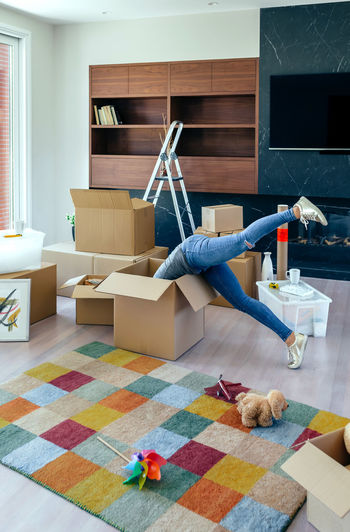 Young woman inside a box while preparing the move Family Fun Happiness Happy Moving Unpacking Apartment Boxes Cardboard Home Interior House Indoors  Inside Legs Lifestyles Living Room Looking New Home One Person Packing Placing Real People Relocating Unrecognizable Person Vertical