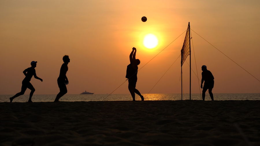 Silhouette People Playing On Volleyball At Beach Against Sky During Sunset