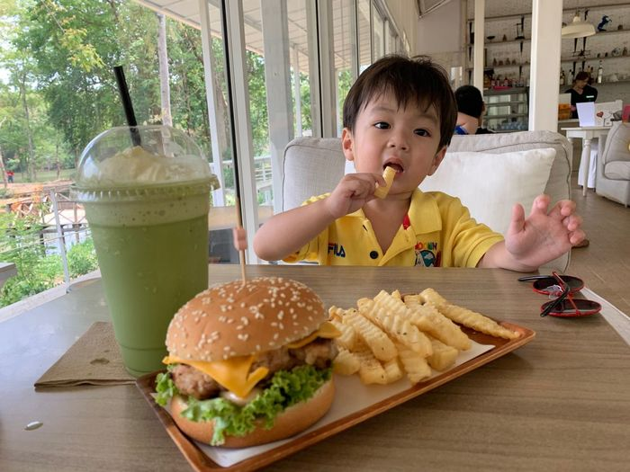 Food And Drink Fast Food Food Unhealthy Eating Ready-to-eat Child Burger Childhood Sandwich Table One Person Restaurant Real People Indoors  Lifestyles Freshness Front View Boys Portrait Hamburger Fried Innocence Glass
