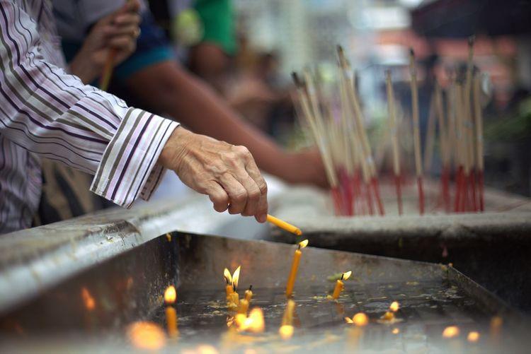 Cropped Image Of Man Burning Candle