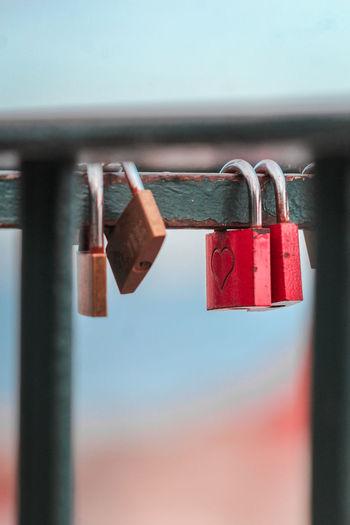 Close-up of padlocks hanging on railing against sky