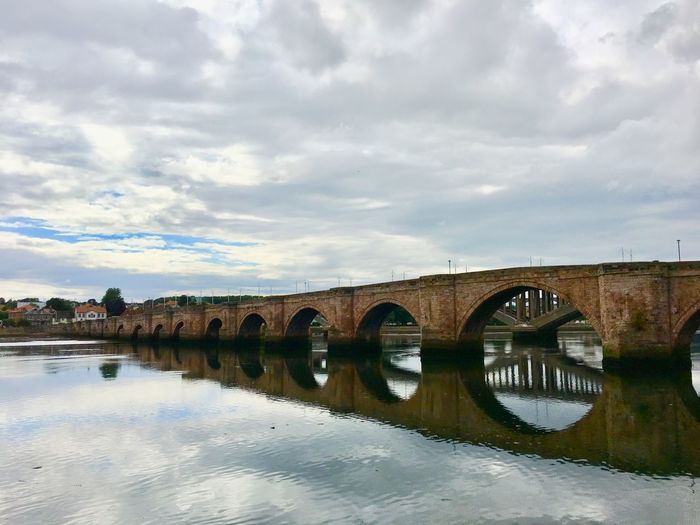 Arch bridge over river against sky