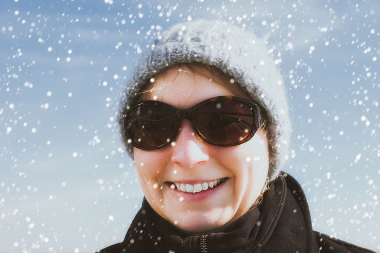 Portrait of smiling woman wearing sunglasses during snowfall