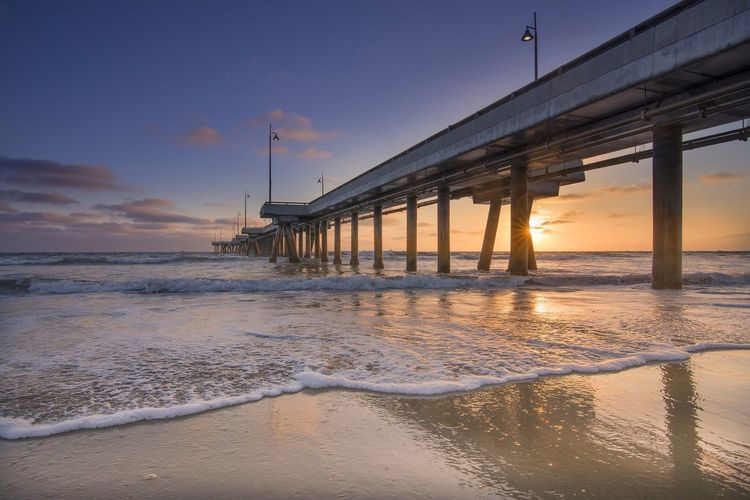 View Of Pier On Beach At Sunset