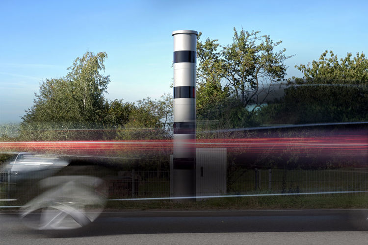 Blurred motion of vehicles on road against sky