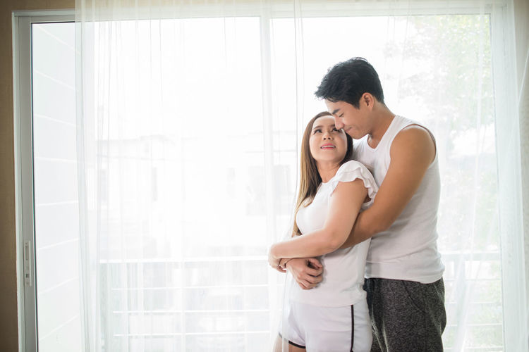Couple cuddling by window at home