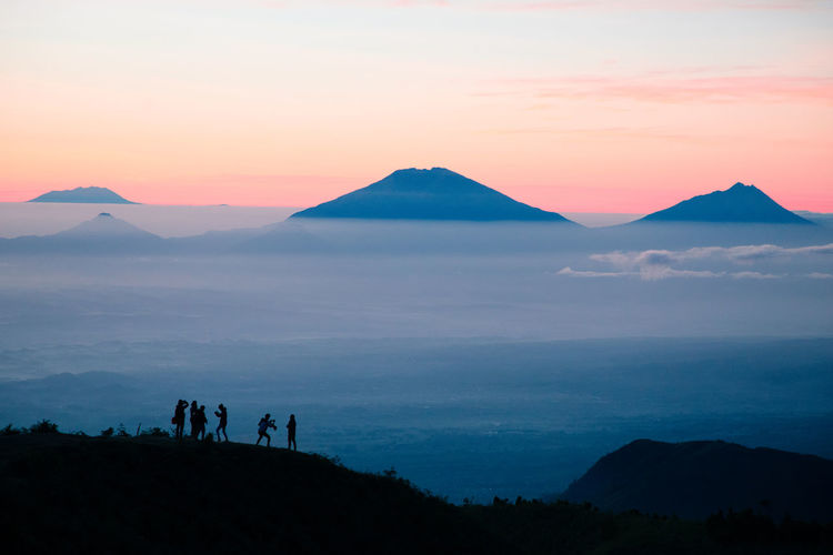 Sky Mountain Scenics - Nature Beauty In Nature Sunset Tranquil Scene Tranquility Nature Non-urban Scene Silhouette Environment Idyllic Landscape Group Of People Mountain Range Land Orange Color Real People Lifestyles Leisure Activity Outdoors Mountain Peak Dream Silhouette Golden Hour