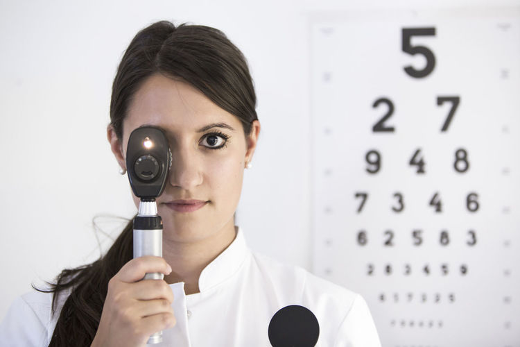 Portrait of young woman holding eye testing equipment