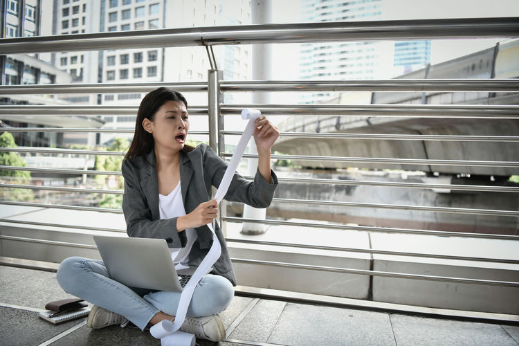 Worried businesswoman looking bill while sitting on floor against railing