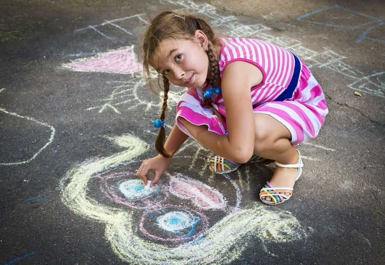 Smiling girl drawing with chalk on street