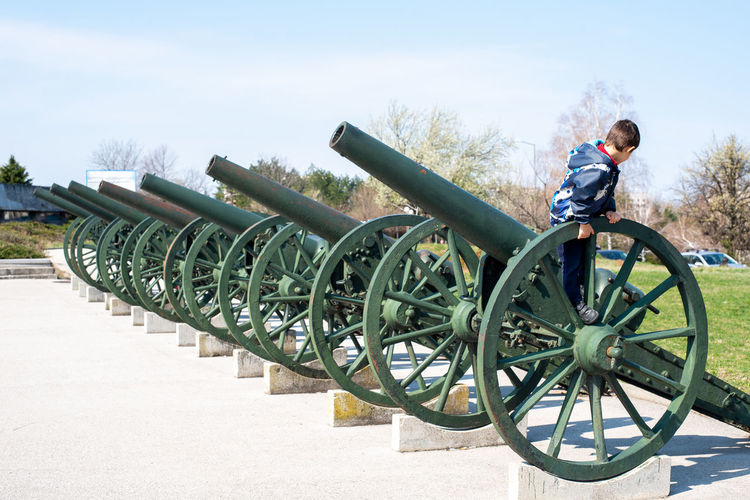 Side view of boy standing on gun barrel against sky