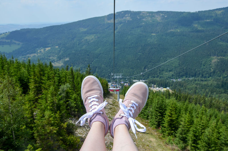 Low section of woman wearing shoes against ski lift and sky