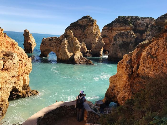 High Angle View Of Woman Standing On Observation Point By Sea At Ponta Da Piedade