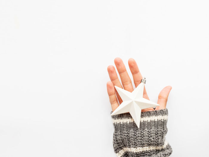 Close-up of hand holding umbrella against white background
