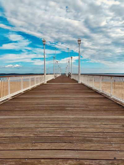 View of pier on sea against cloudy sky