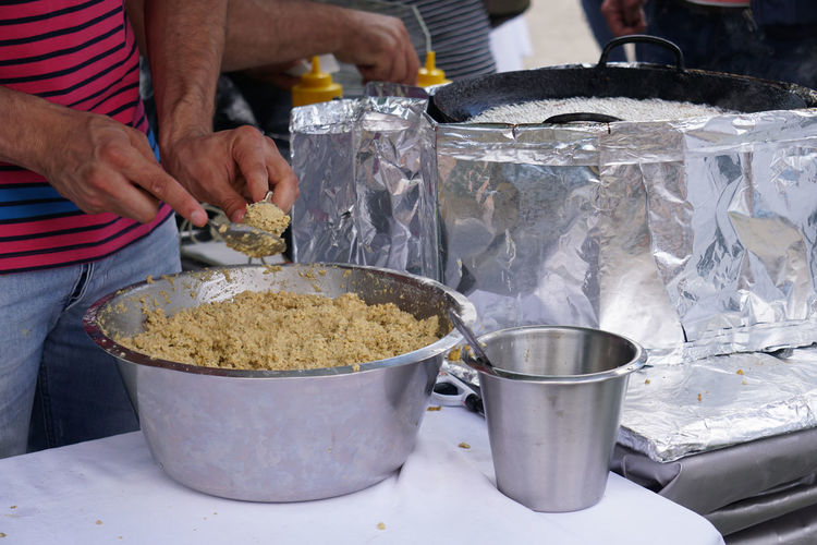 Midsection of man preparing falafel on stall at market