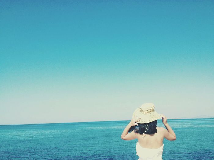 Rear view of woman by sea against clear blue sky