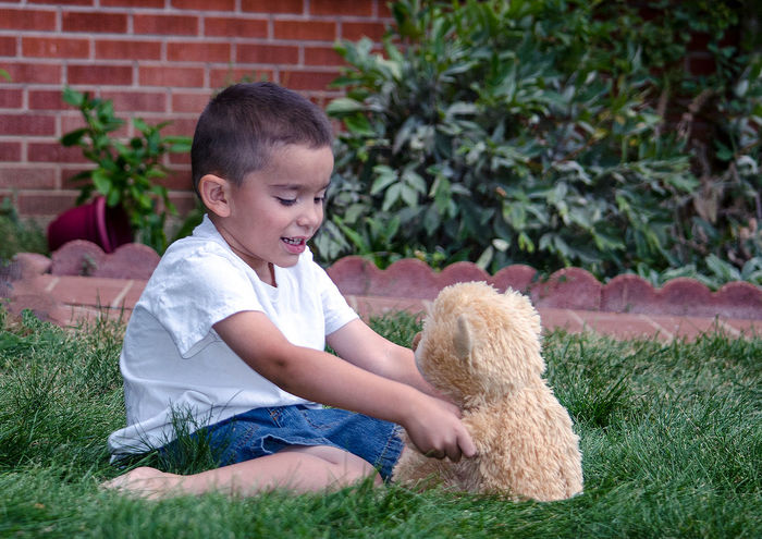 conversation with my bear friend; this little boy knows friends come in all shapes and sizes and best when stuffed with fluff Fun Imagination Animal Themes Childhood Friendship Front Or Back Yard Full Length Grass Happiness Hispanic Interact Kid Lifestyles Mammal One Person Outdoors People Playing Real People Sitting Smiling Stuffed Teddy Bear Toy