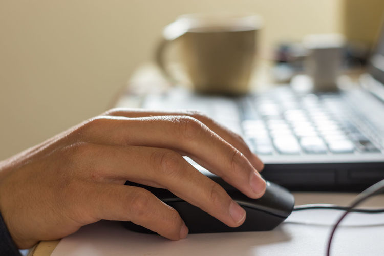 Close-up of hand using laptop on table
