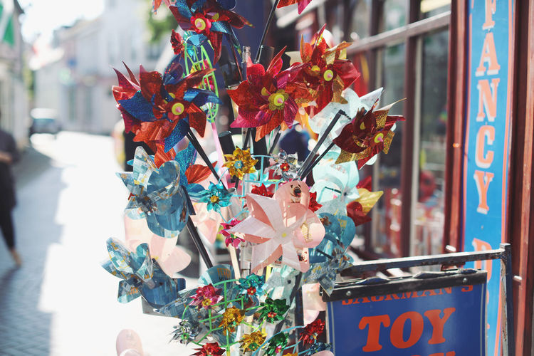 Multi Colored Large Group Of Objects Decoration Day For Sale No People Focus On Foreground Retail  Creativity Outdoors Art And Craft Celebration Pinwheel Toy Choice Variation Hanging Close-up Small Business Market Stall Glass - Material Retail Display