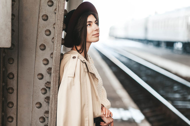 Full length of young woman standing on railroad station platform