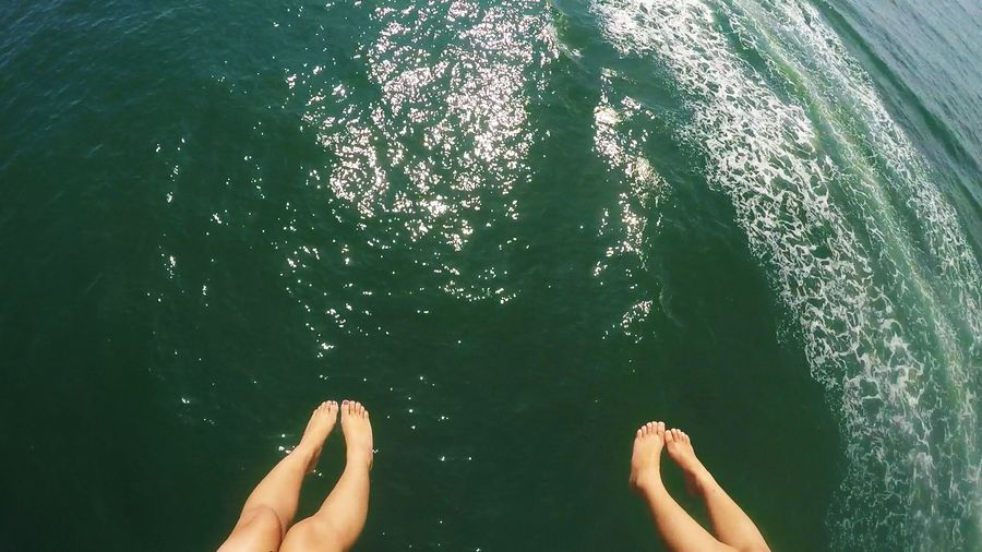High Angle View Of People Legs Over Sea