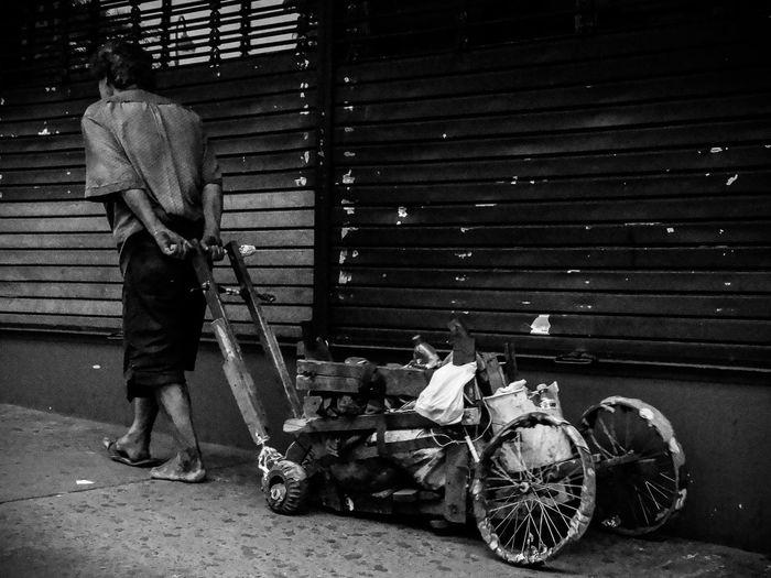Homeless man pulling messy cart on sidewalk in city