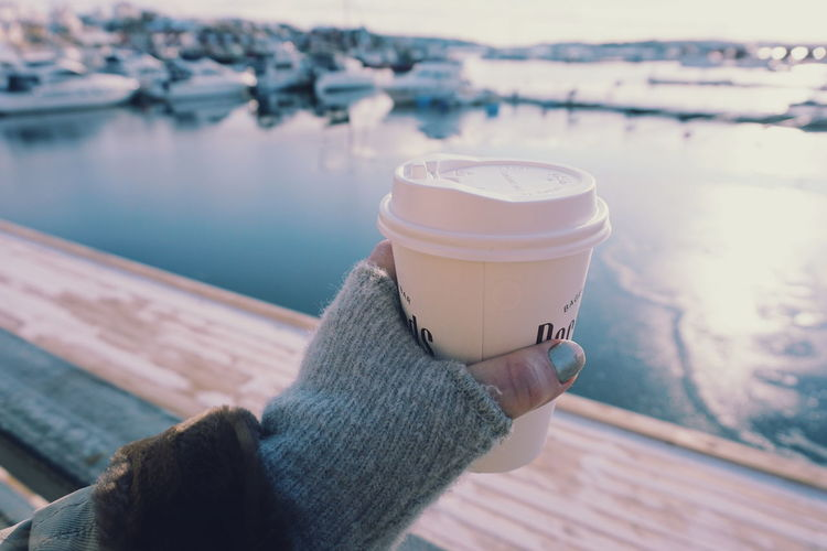 Cropped Hand Holding Coffee Against River