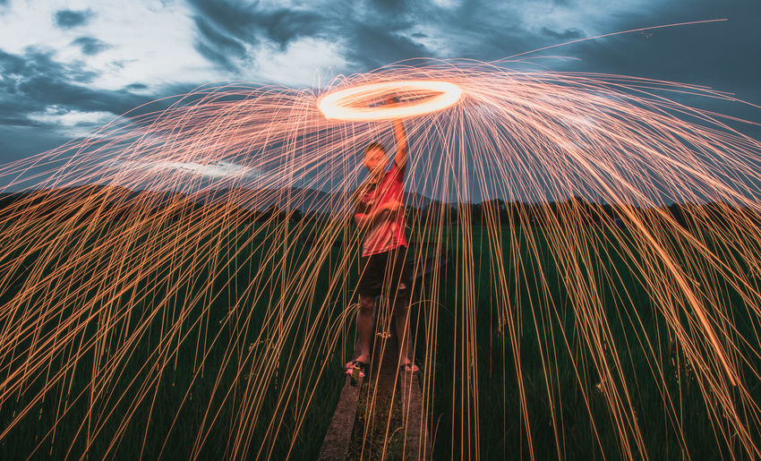 Low angle view of man spinning wire wool against sky during dusk