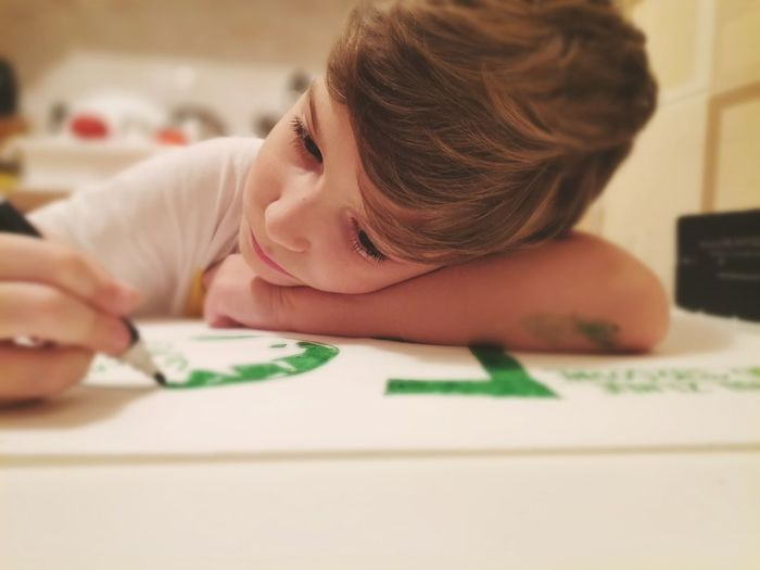 Small boy drawing on the paper at home.