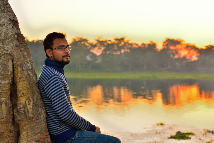 Young man sitting by tree at lakeshore against sky during sunset