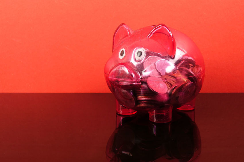 Saving concept with red piggy bank on red background. Piggy Bank Animal Representation Close-up Coin Colored Background Conceptual Photography  Container Drink Food And Drink Glass - Material High Angle View Indoors  Investment Mask No People Pink Color Red Red Background Representation Saving Concept Single Object Still Life Studio Shot Table Transparent