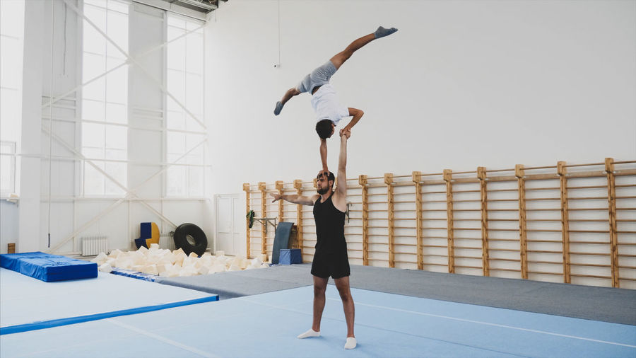 Instructor with teenage boy practicing gymnastics in club