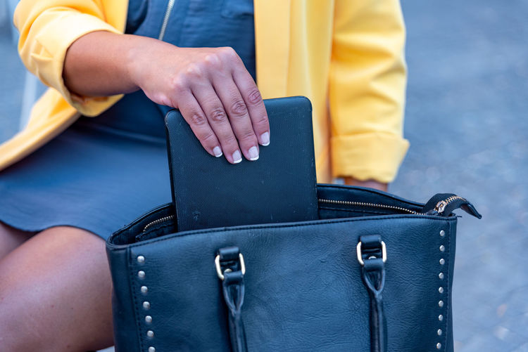 Unrecognizable white business woman saving a device in her handbag