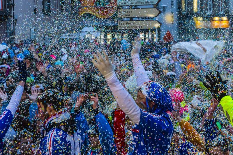 Crowd Throwing Colorful Confetti In City During Celebration