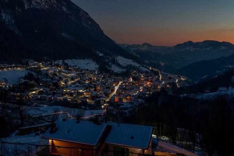 Mountain village icon snow at sunset