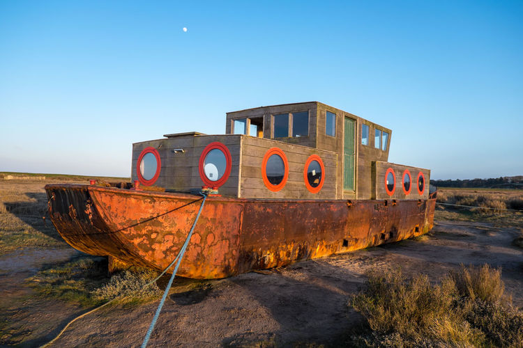 Abandoned boat moored on beach against clear sky