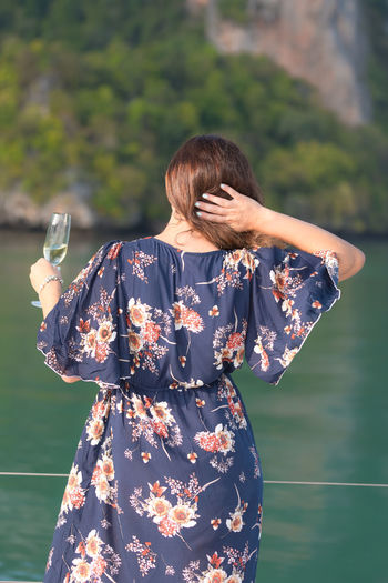 One Person Real People Three Quarter Length Standing Lifestyles Casual Clothing Holding Focus On Foreground Women Leisure Activity Rear View Adult Day Clothing Nature Water Outdoors Hairstyle Floral Pattern Glass