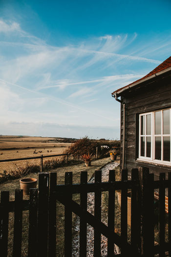 Wooden fence by wooden house against sky near field in english village