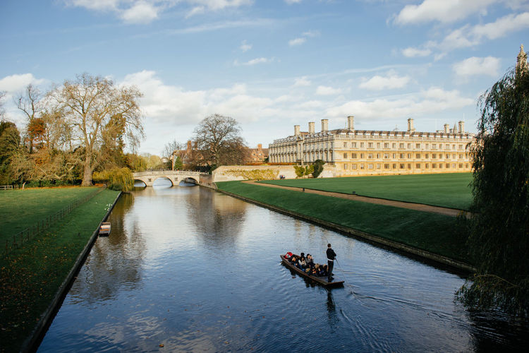 People rowing boat in river cam at university of cambridge campus