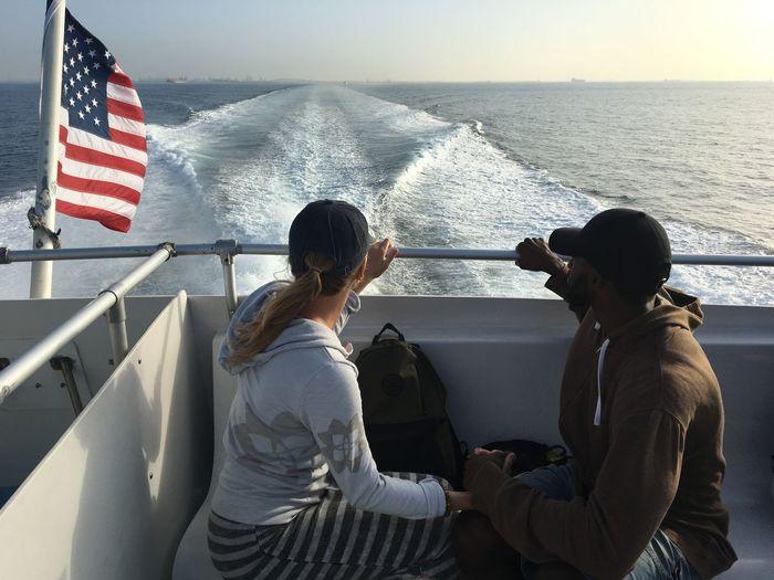 Women sitting on boat in sea against sky
