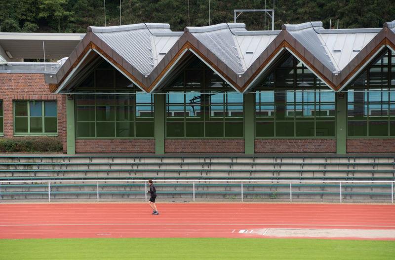 Built Structure Casual Clothing City Life Grass Jog Jogger Jogging Leisure Activity Lifestyles Multi Colored Red Runner Sport Sportplatz Sports Stadion Stadium