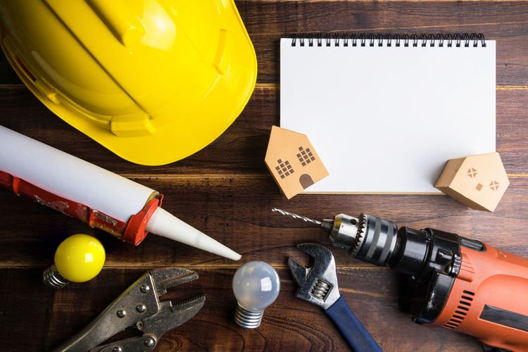 Blank notebook white paper and construction tools on wooden background with copy space.Real estate concept, New house concept, Finance loan business concept, Repair maintenance concept Balloon Close-up Communication Directly Above Equipment Hardhat  High Angle View Indoors  Large Group Of Objects No People Paper Pen Still Life Table Tape Measure Text Tool Wood - Material Work Tool Yellow