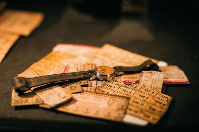 Close-up of old wristwatch with papers on table