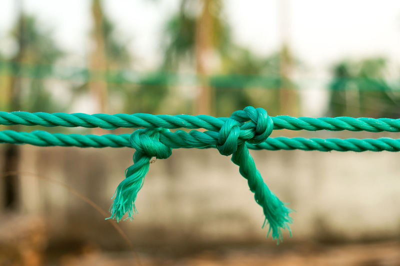 Close-up of rope fence on field